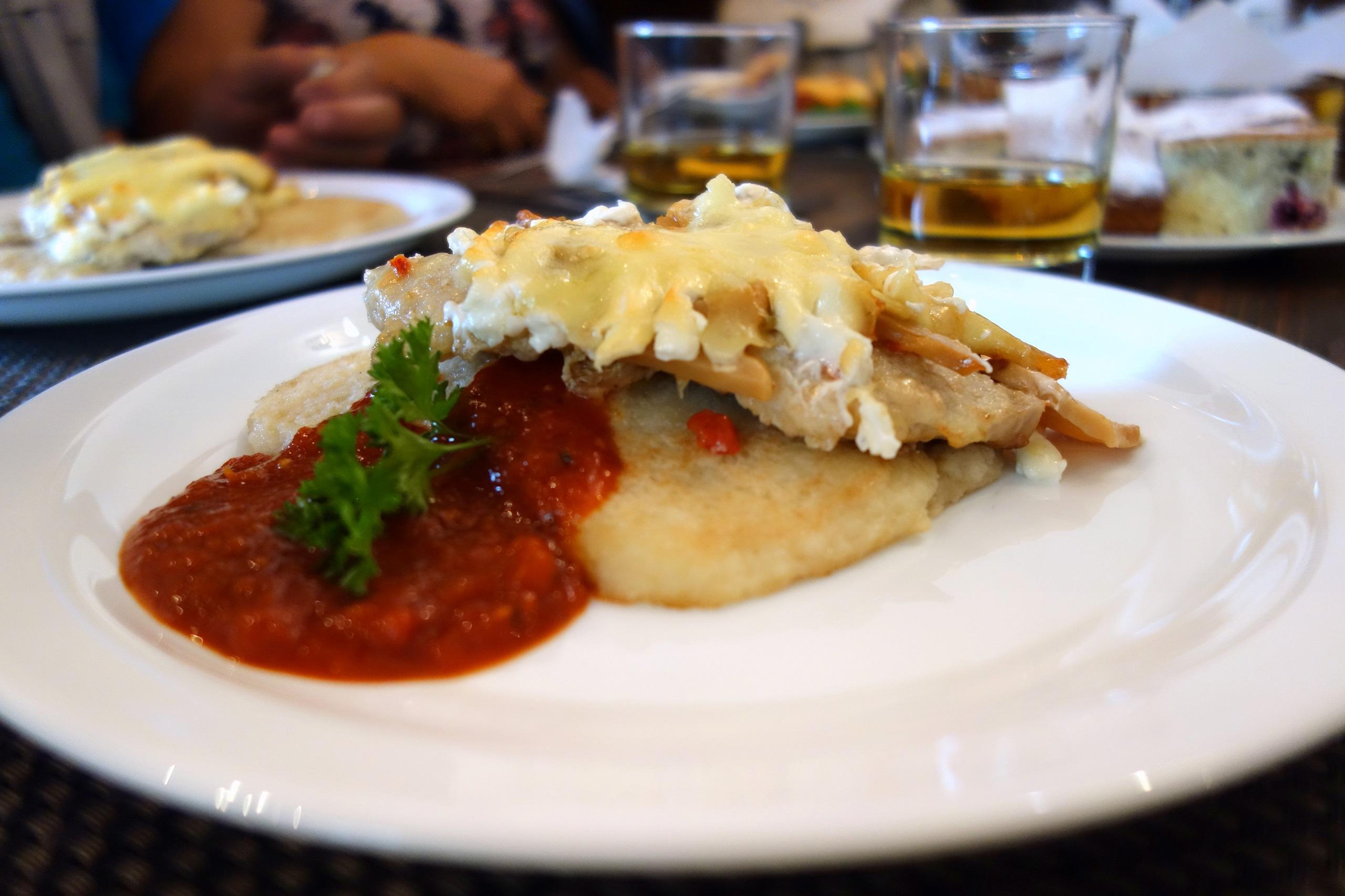 Kuchnia białoruska - placki ziemniaczane z kotletem schabowym zapiekanym w serze i pieczarkach